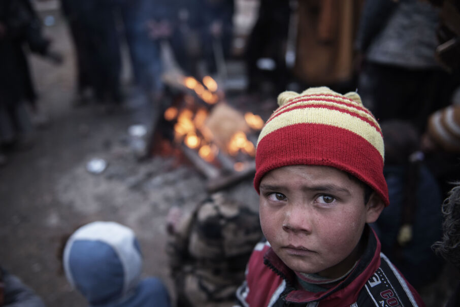 4 marca 2017 roku, Irak. Dziecko ogrzewa sięprzy ogniu po ucieczce z terenów ogarniętych walkami między dżihadystami a siłami irackimi