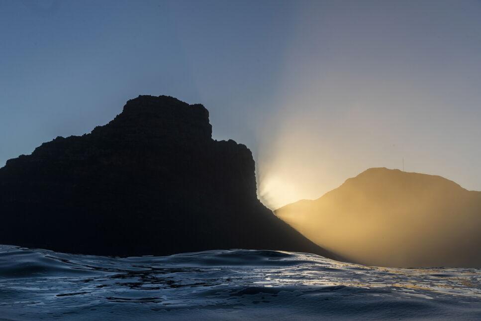 Słońce wschodzi za górą Sentinel widzianą z rafy Dungeons na Oceanie Atlantyckim, pod Kapsztadem, RPA