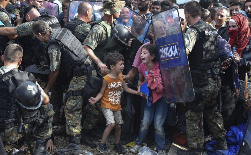 """Zwycięska fotografia """"UNICEF Zdjęcie Roku 2015"""" zrobiona przez Georgiego Licovskiego z European Pressphoto Agency. Zdjęcie pokazuje płaczące dzieci migrantów na greckiej granicy, otoczone przez kordon macedońskich policyjnych sił specjalnych."""