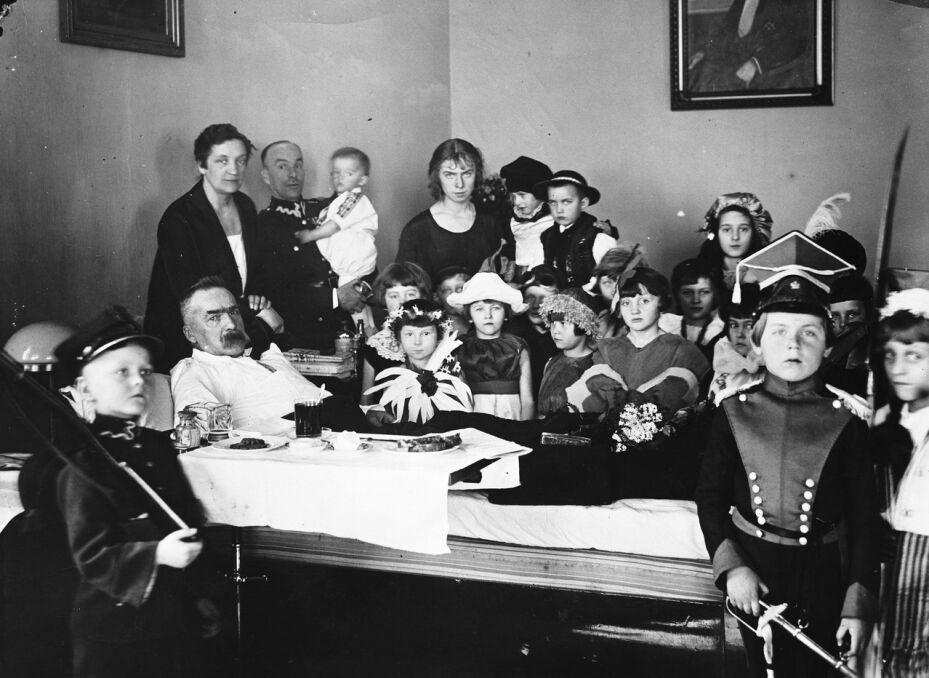 Józef Piłsudski (w łóżku) z żoną Aleksandrą Piłsudską (stoi nad marszałkiem) podczas odbierania życzeń od dzieci przybyłych do Belwederu. 19 marca 1927 roku