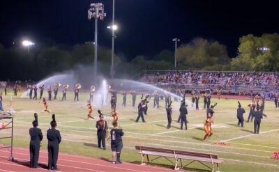 Próba orkiestry na szkolnym boisku przerwana przez automatyczne zraszacze