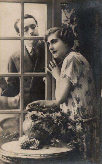 Kobieta przy przeszklonych drzwiach, za którymi stoi mężczyzna