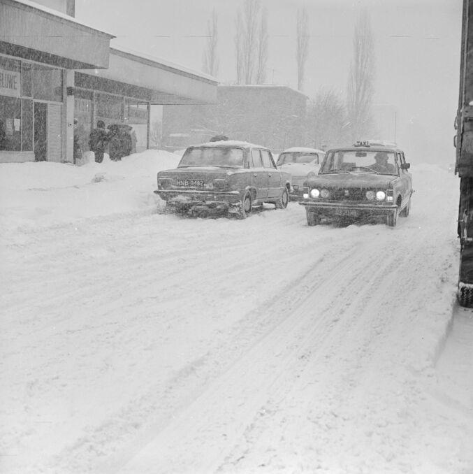Taksówka na zaśnieżonej warszawskiej ulicy. Pługi śnieżne nie nadążały z usuwaniem zasp zalegających na jezdniach